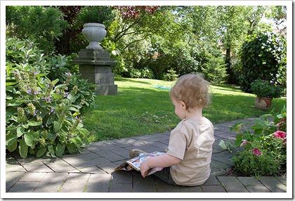 Bebe lisant seul dans le jardin